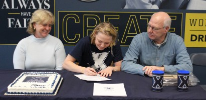 Clare Bosse signs her National Letter of Intent to swim for Xavier University while her parents, ...
