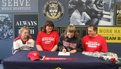 Amber Fischer signs her National Letter of Intent while her parents, John and Helen, and sister, ...