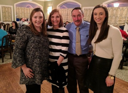 Hilary is pictured at her retirement party with her husband Kelly and daughters, Janine '10 a...