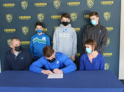 Joe Krauza signs his National Letter of Intent as his parents, Connie and Andrew, and brothers Ma...
