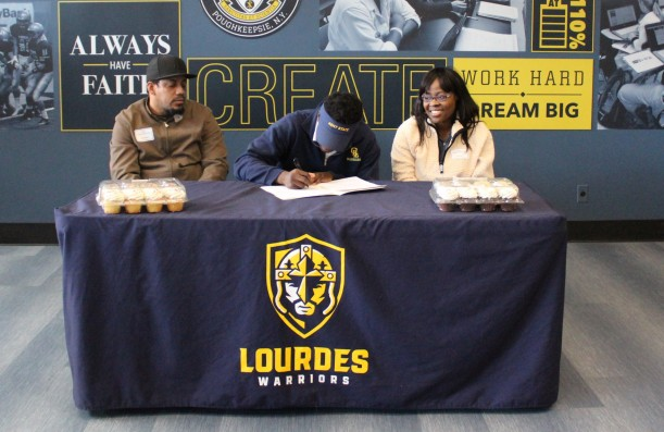 Jaheim signs his National Letter of Intent while his mother, Erica Springer, and stepfather, Kevi...