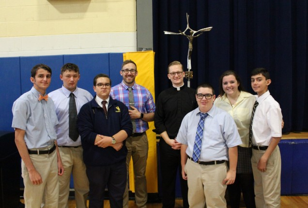 Father Connolly and Mr. Herles pose with student Campus Ministry members, Gerard Junjulas, Salvat...